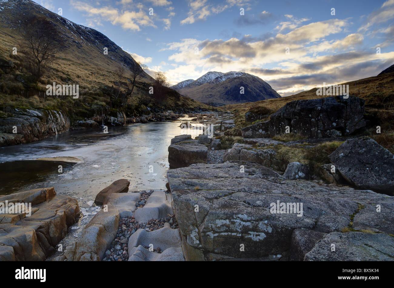 Vista invernale parzialmente lungo-fiume congelato Etive verso montagne distanti, Glen Etive, Rannoch Moor, Highland, Immagini Stock