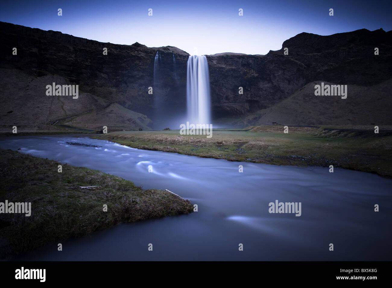 Cascata Seljalandsfoss catturato al crepuscolo mediante esposizione a lungo per registrare il movimento in acqua, Immagini Stock