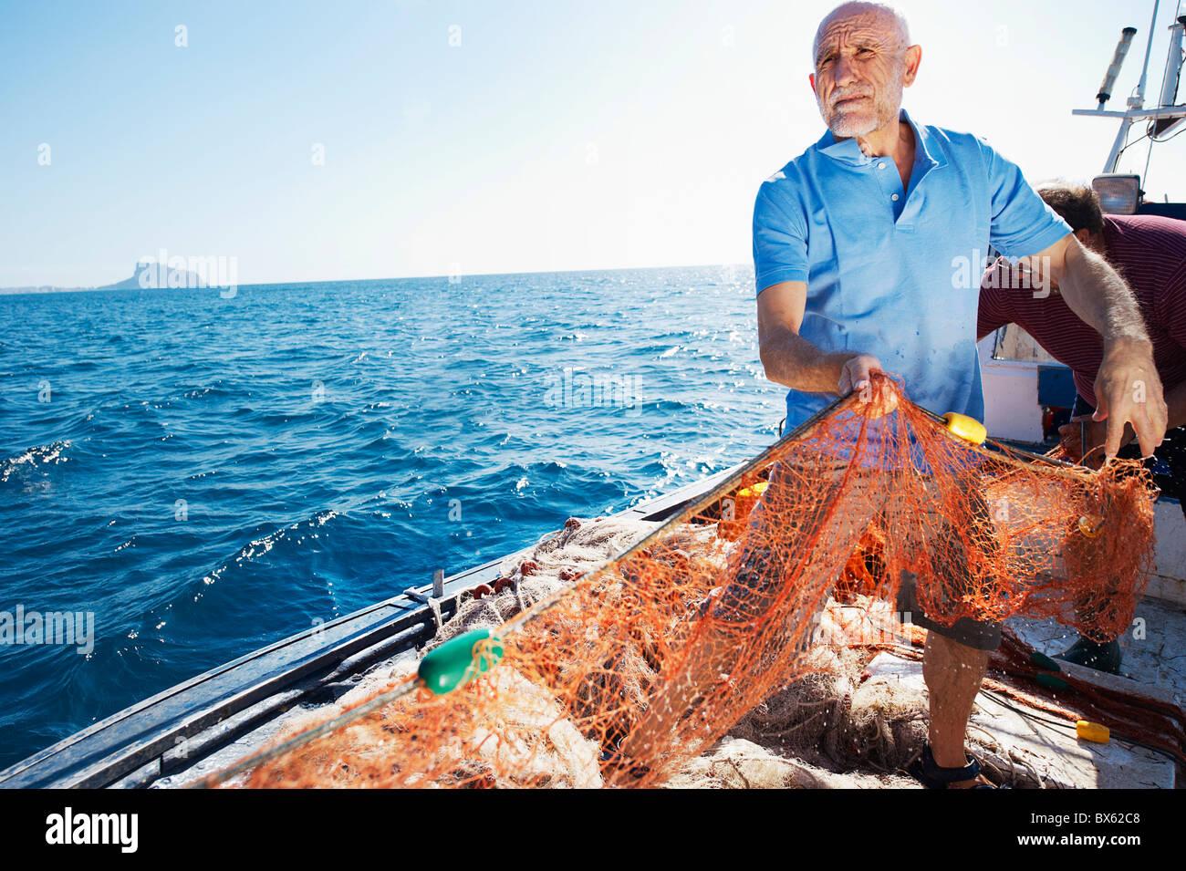 Pescatore sulla barca tirando in reti Immagini Stock