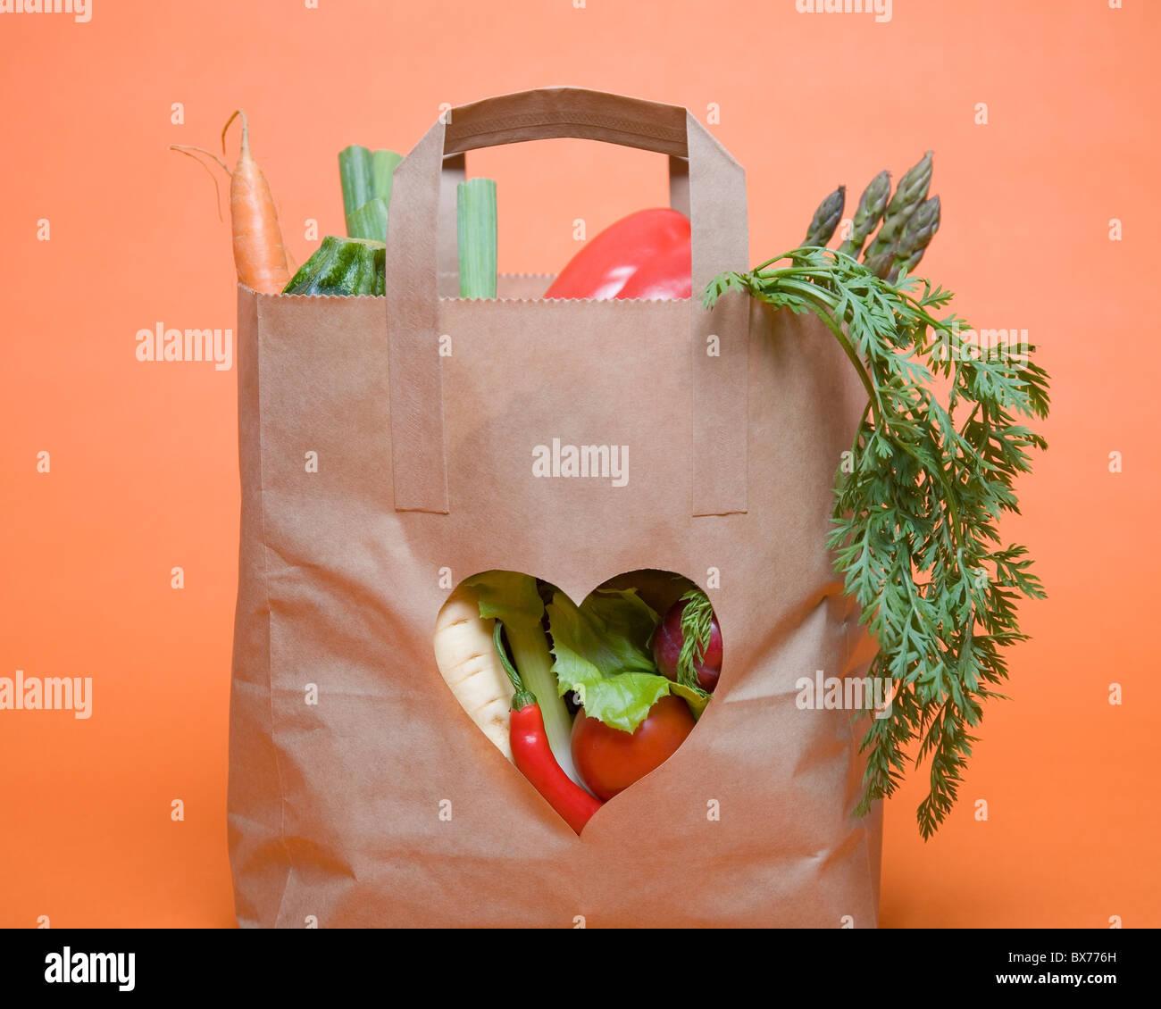 Verdure in borsa con il simbolo del cuore Foto Stock