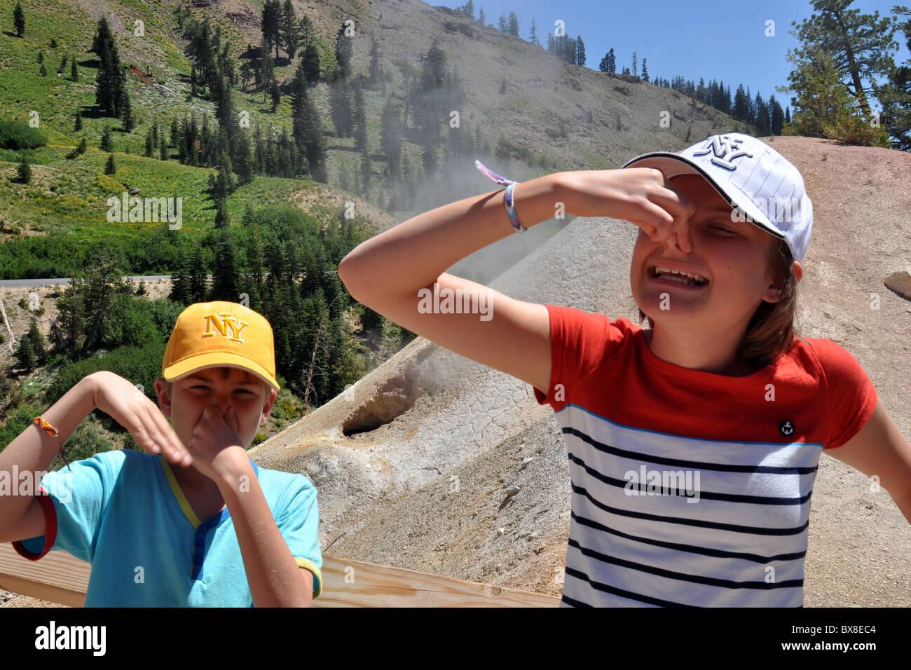 Un ragazzo e una ragazza non piace l'odore solforico nel parco vulcanico sul Monte Lassen National Park, California, Immagini Stock
