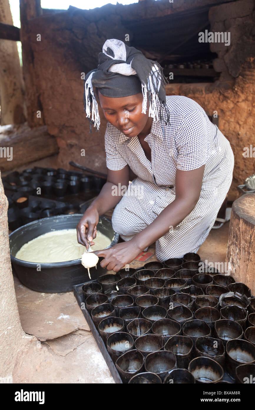 Un baker (Rehama Mbabazi) versa la pastella in un cakepan nel villaggio Mutukula, Iganga distretto, Uganda orientale, Immagini Stock