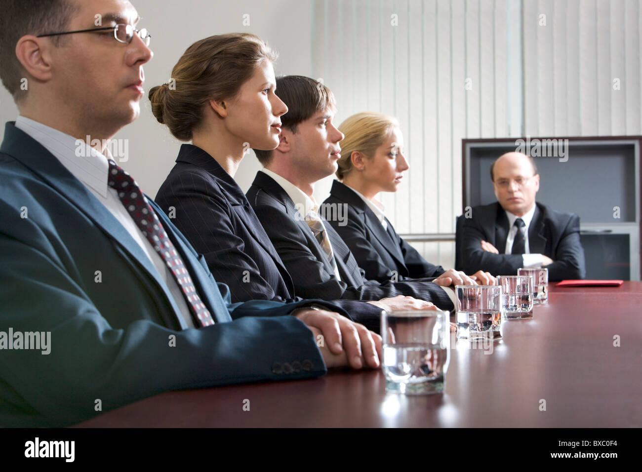 Tense i giovani sono seduti a tavola in una linea e loro orinato boss Immagini Stock