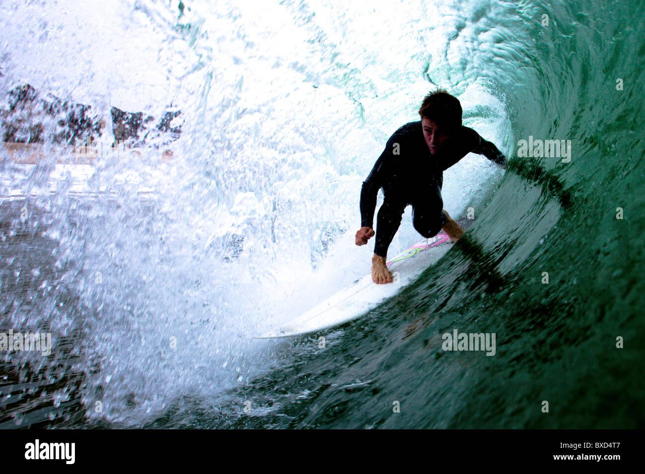 Un maschio avanzata surfer cavalca il tubo. Immagini Stock