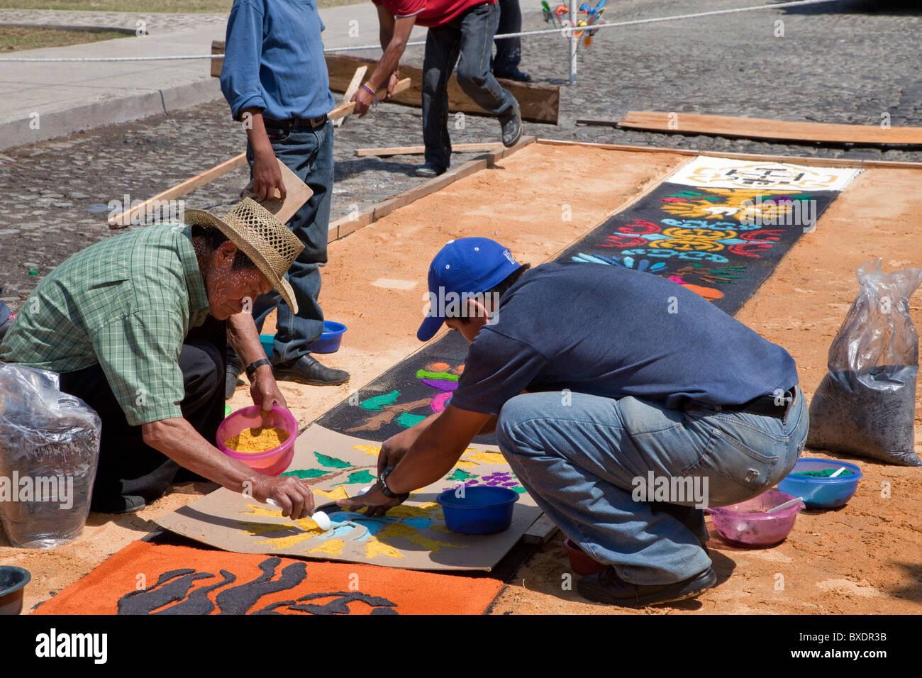 Antigua, Guatemala. Utilizzando uno stencil per terminare un alfombra di segatura colorata in anticipo di una processione Immagini Stock