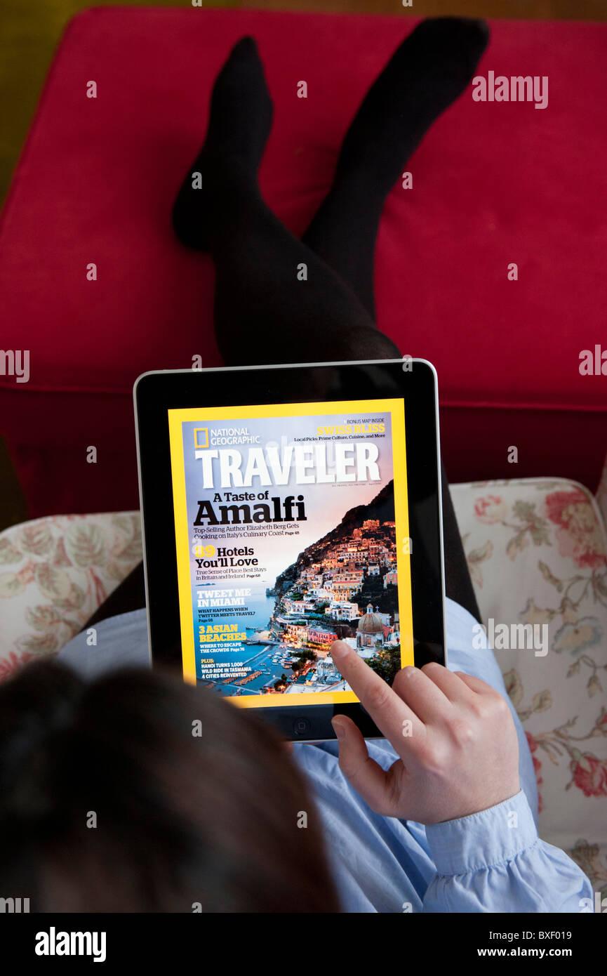 La donna la lettura di National Geographic Traveler online travel magazine applicazione su un computer tablet iPad Immagini Stock