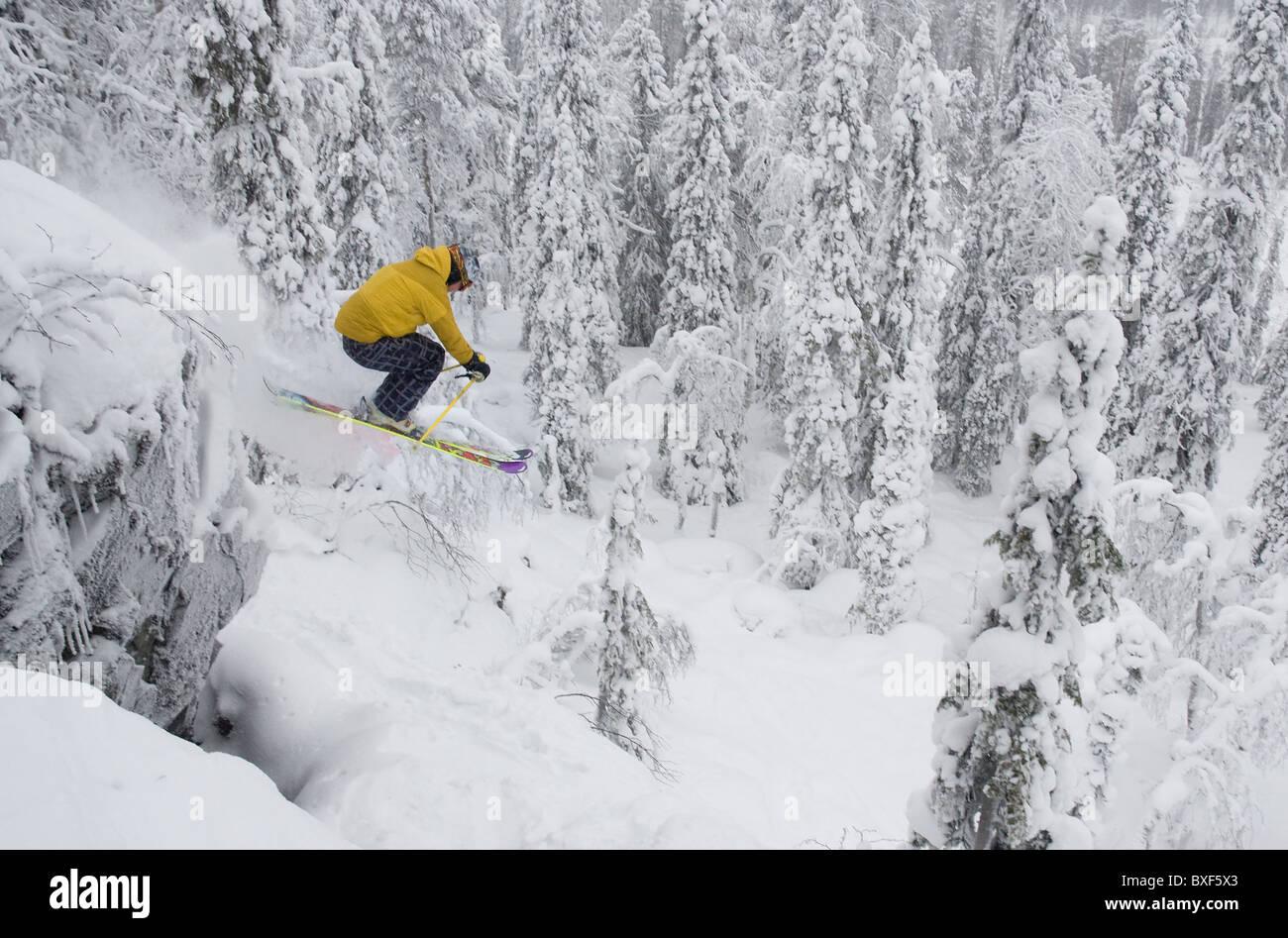 Un maschio libero sciatore saltare giù una scogliera in Iso-Syöte, Finlandia Immagini Stock