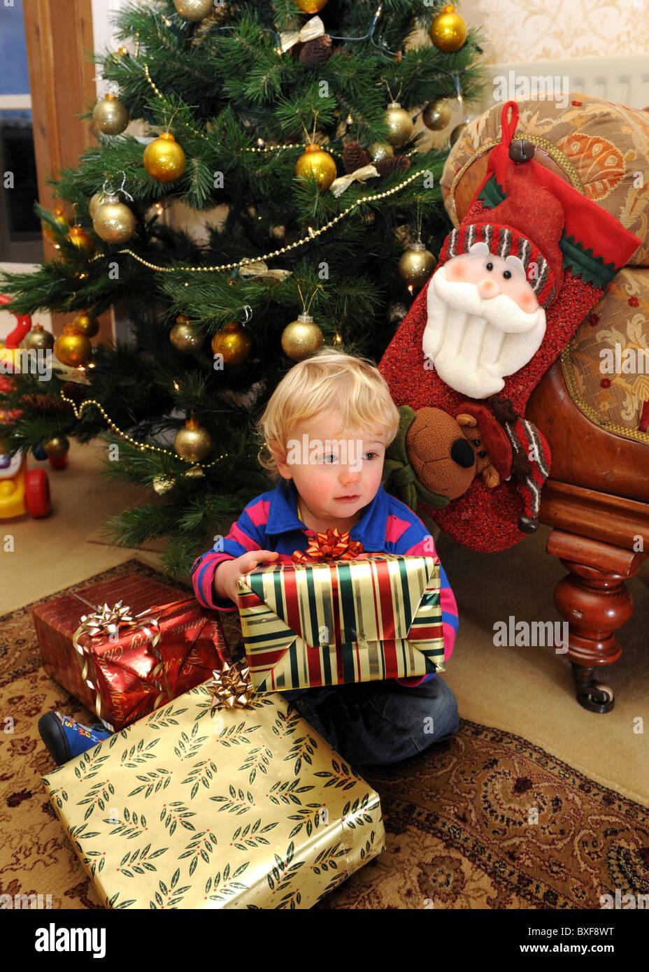 Apertura Regali Di Natale.Baby Boy Apertura Regali Di Natale Nella Parte Anteriore Dell Albero Di Natale Foto Stock Alamy
