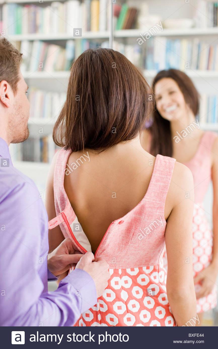 L'uomo zippare moglie del vestito per lei Immagini Stock