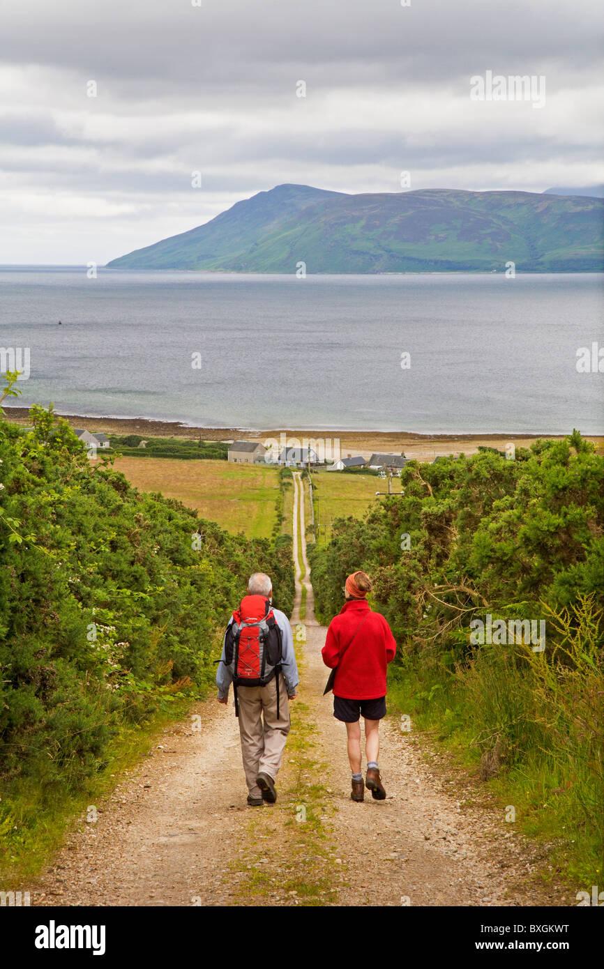 Walkers avvicinando Skipness sul modo di Kintyre. Arran è in background. Immagini Stock