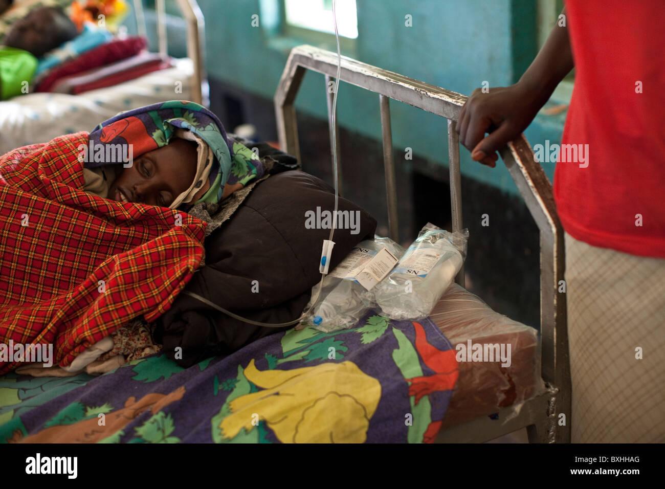 Una donna si addolora per sua figlia che muoiono di AIDS in Amuria, Uganda, Africa orientale. Immagini Stock