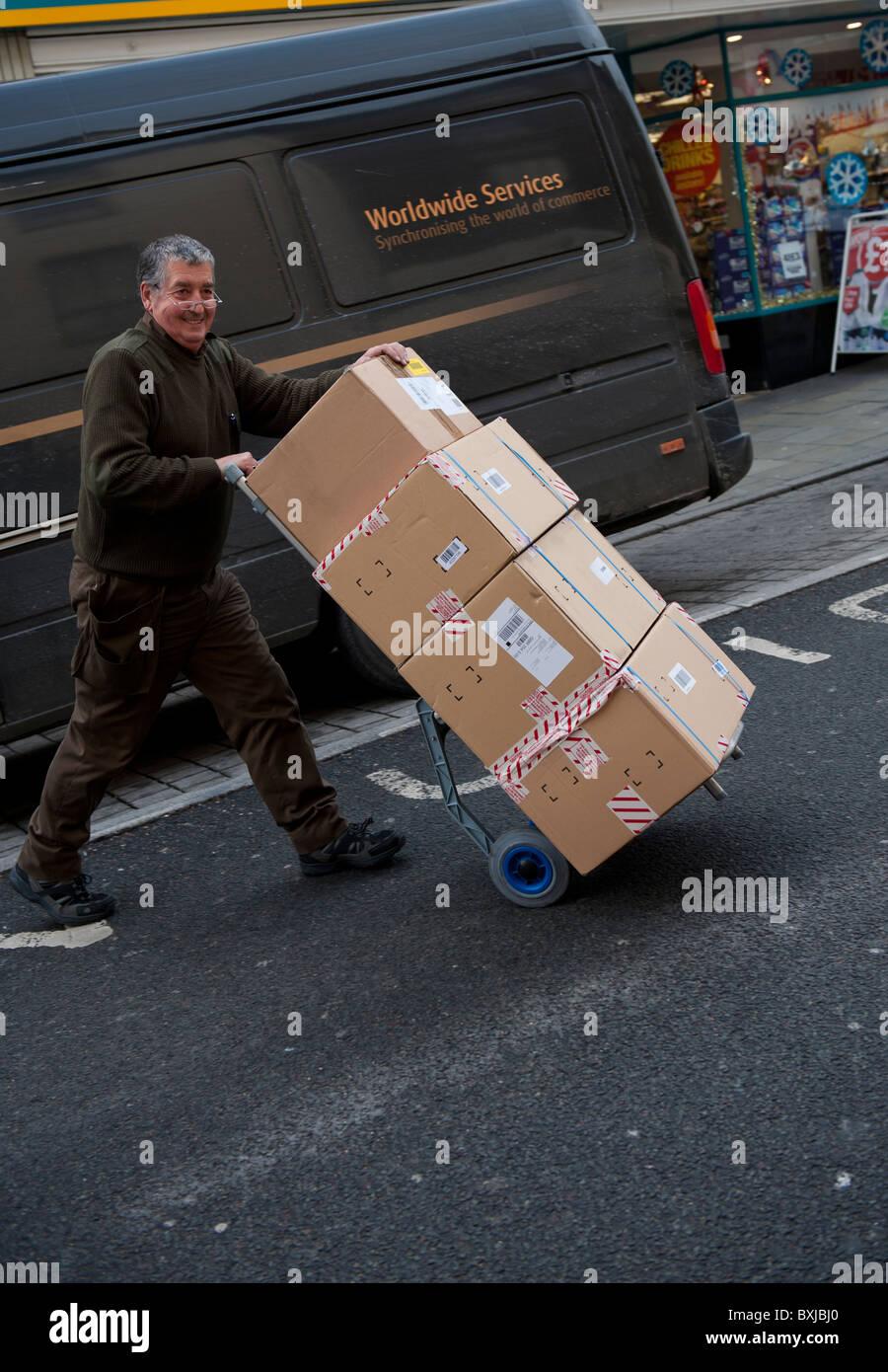 Un UPS uniti i pacchi servizio servizio di corriere uomo offrendo una pila di pacchi per un cliente, REGNO UNITO Immagini Stock