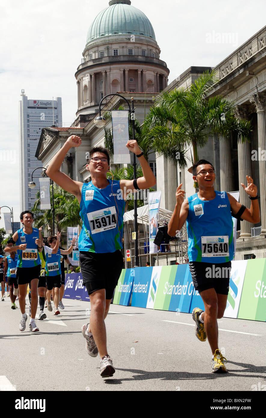 Guide di scorrimento a Singapore Marathon 2010, la Corte suprema e il Municipio in background. Immagini Stock