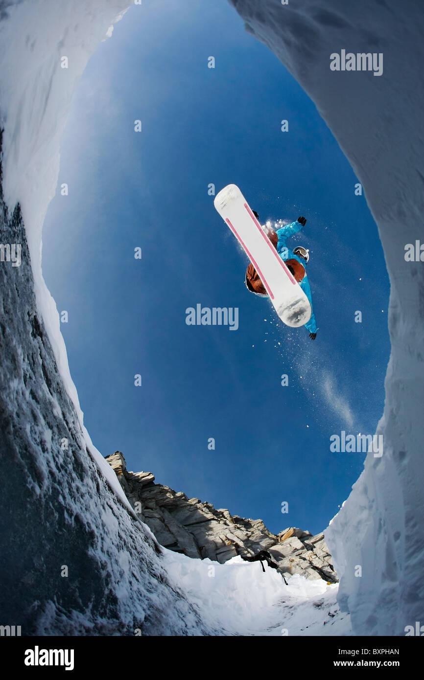 Vista dal di sotto di agile snowboarder nel salto in alto oltre il cielo blu Immagini Stock