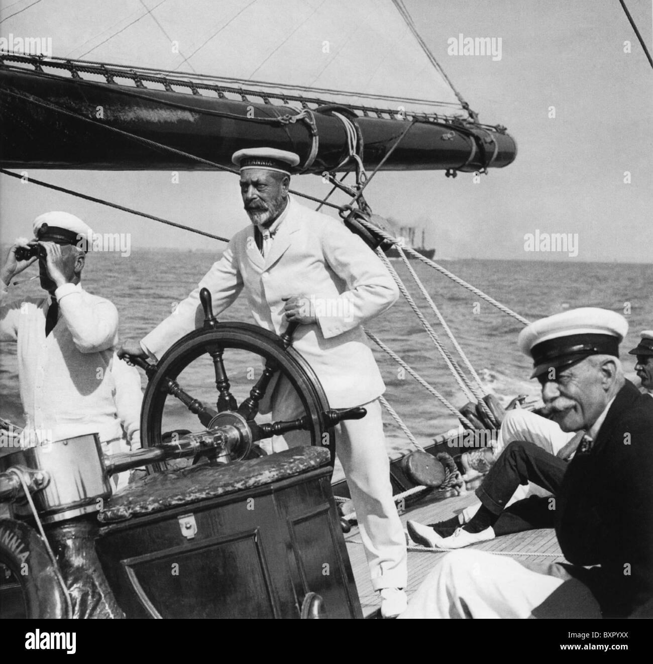 Re Giorgio V (1865-1936) al timone del suo yacht Britannia off Cowes nel 1924 Immagini Stock