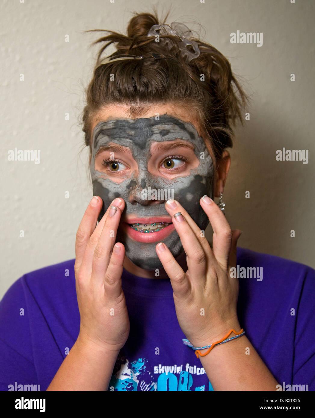 Una ragazza adolescente che indossa bretelle su i suoi denti e una bellezza viso maschera si prepara per una data Immagini Stock