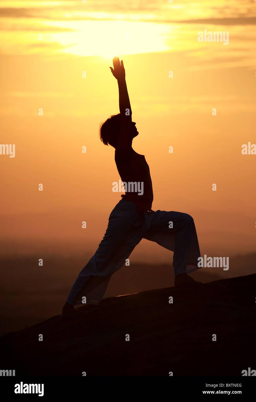 Straniero donna facendo hatha yoga sulle rocce Andhra Pradesh in India del Sud Immagini Stock