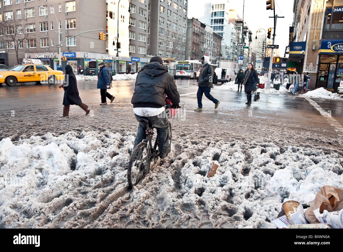 Ciclista esegue lo zoom attraverso l'angolo di strada granite sulla quattordicesima strada a sinistra da dicembre Immagini Stock