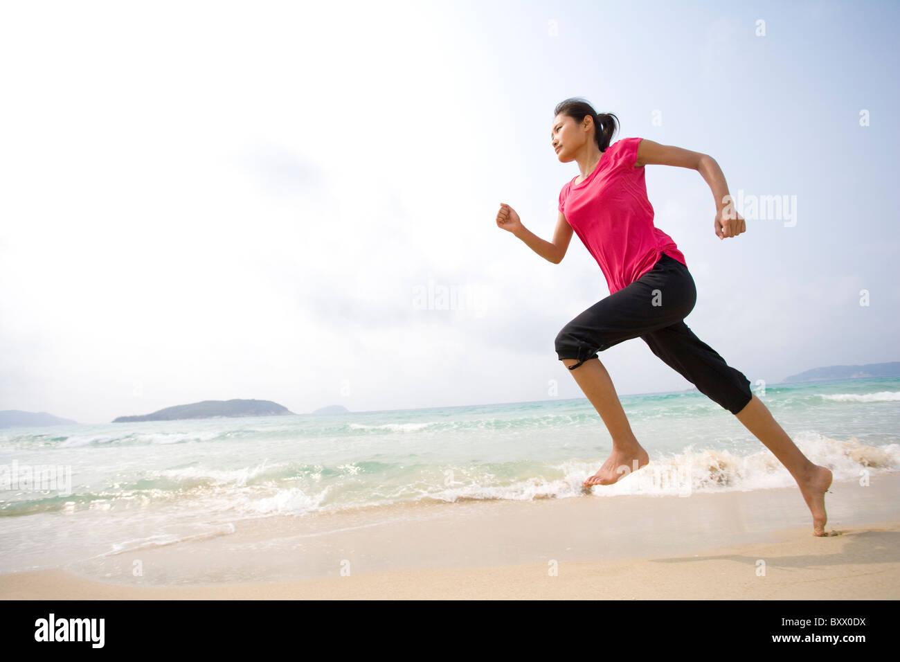 Giovane donna in esecuzione sulla spiaggia Immagini Stock