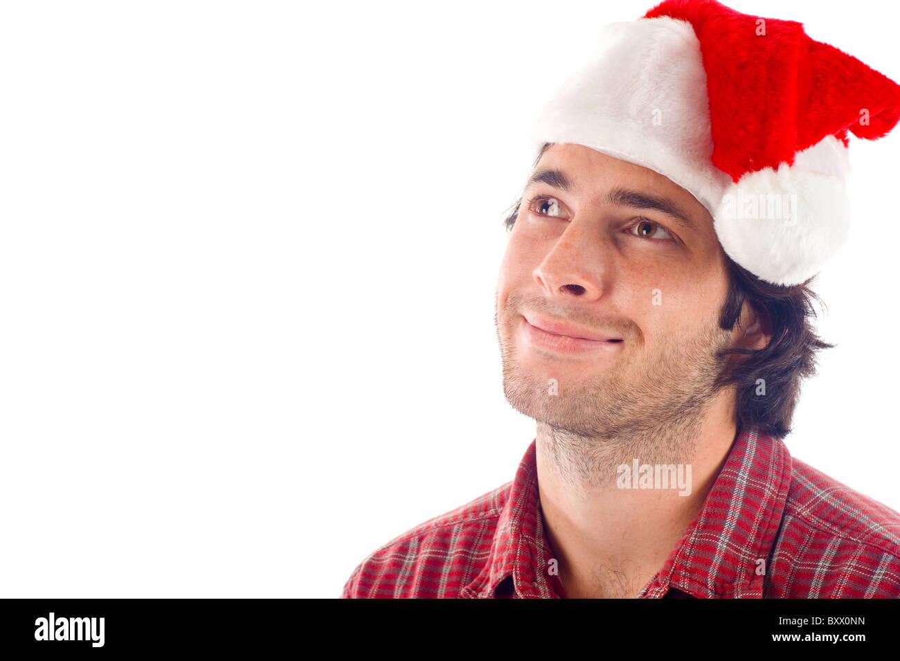 Uomo sorridente con il Natale Red Hat guarda pensieroso -isolate su uno sfondo bianco Immagini Stock