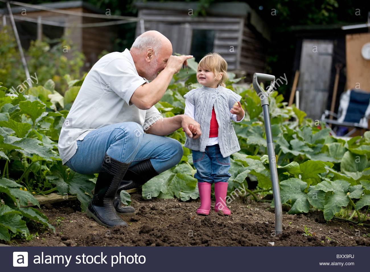 Un nonno che mostra un worm per la sua nipote su un riparto Immagini Stock