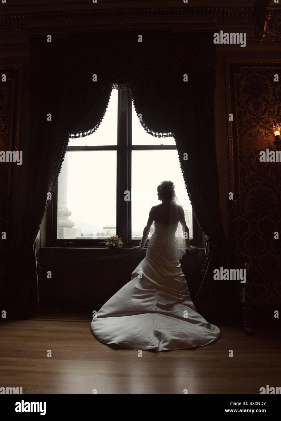 Silhouette della sposa drammatica permanente al grandi finestre Immagini Stock