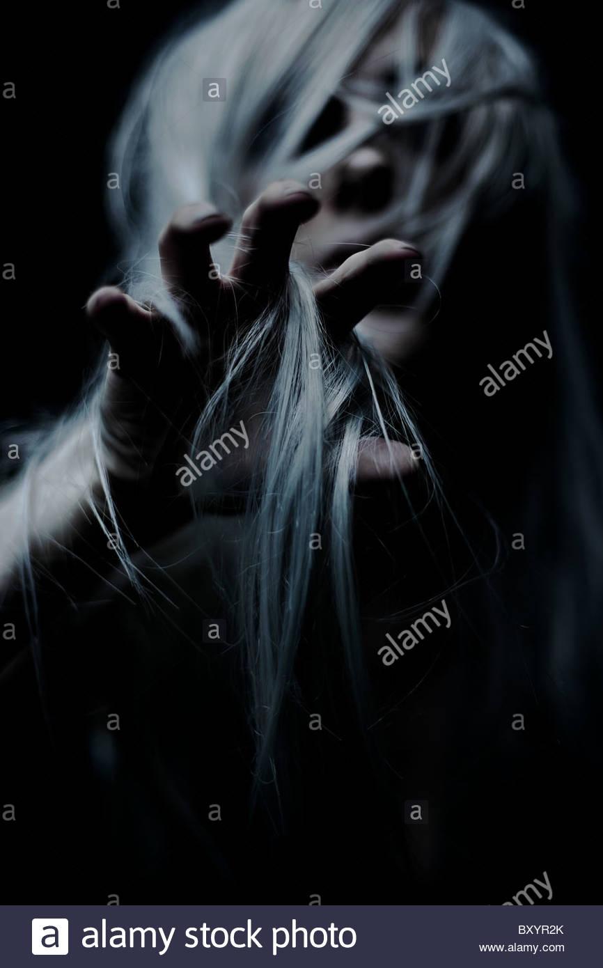 Scary giovane donna con i capelli bianchi raggiungendo fuori mano per afferrare Immagini Stock