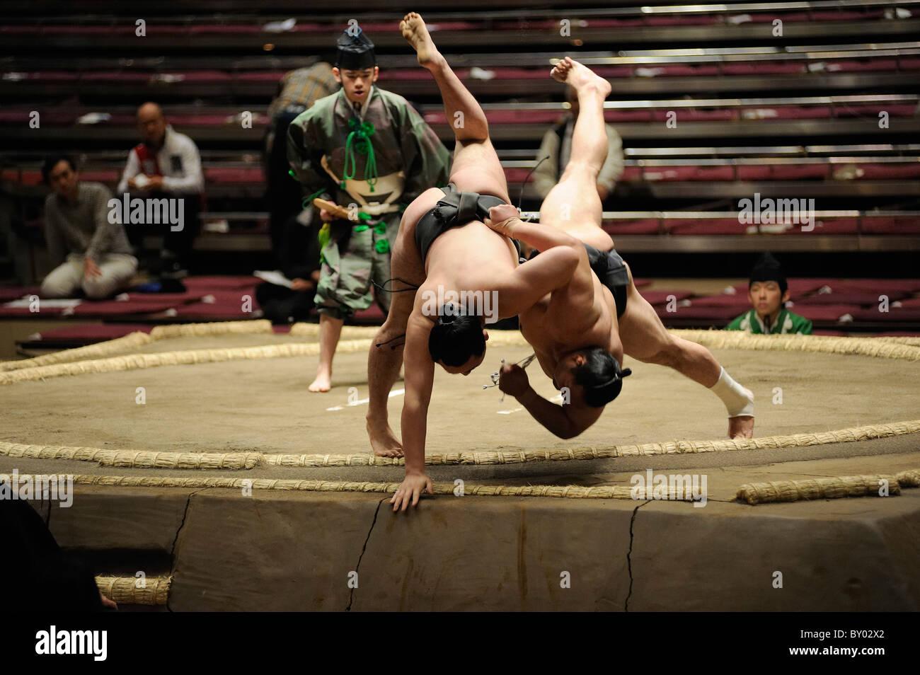Lottatori di Sumo di cadere fuori dal ring, Grandi Campionati di Sumo maggio 2010, Ryogoku Kokugikan, Tokyo, Giappone Immagini Stock