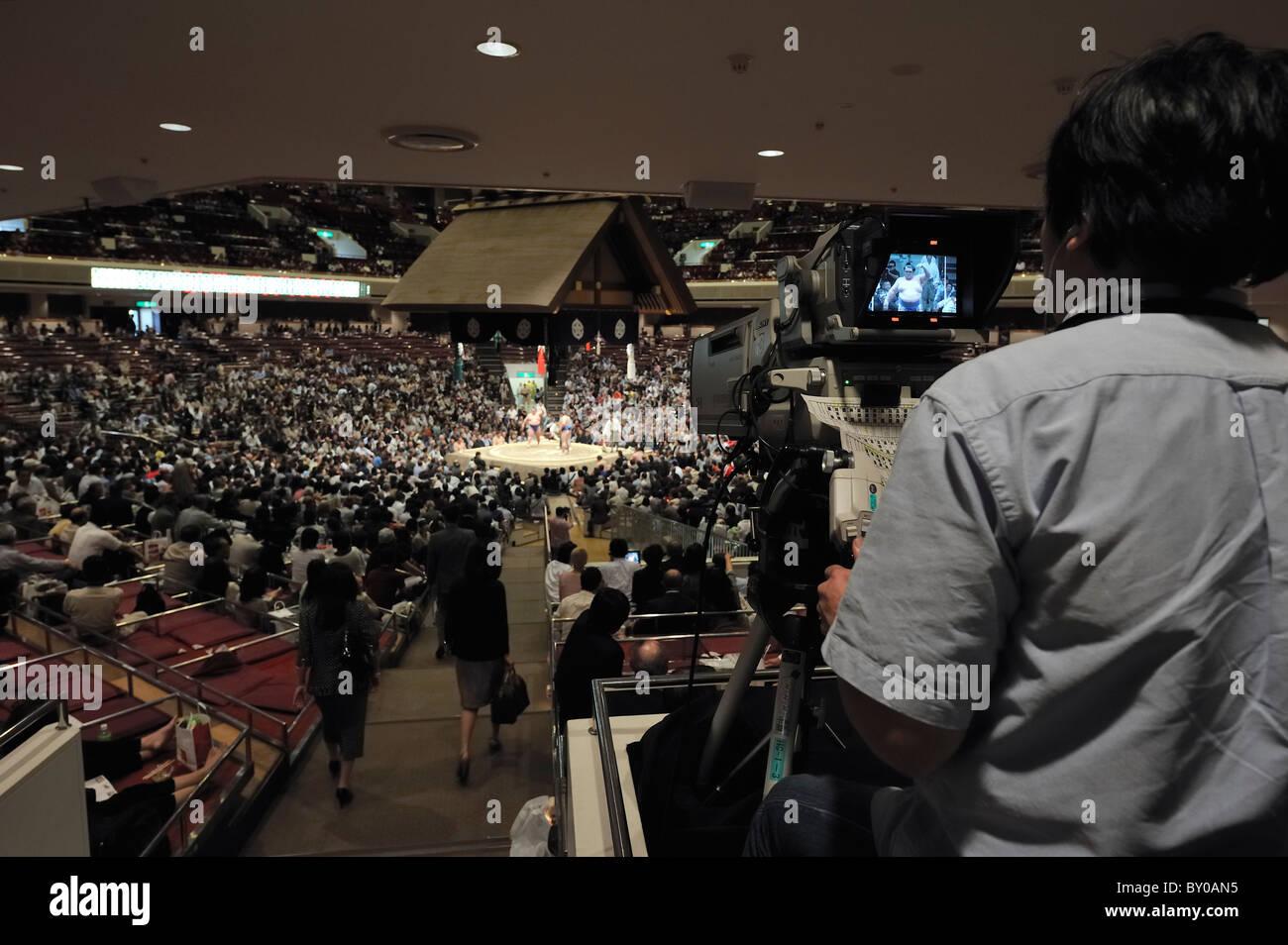 Cameraman rendendo un close-up dell'anello, Grandi Campionati di Sumo maggio 2010, Ryogoku Kokugikan, Tokyo, Giappone Foto Stock