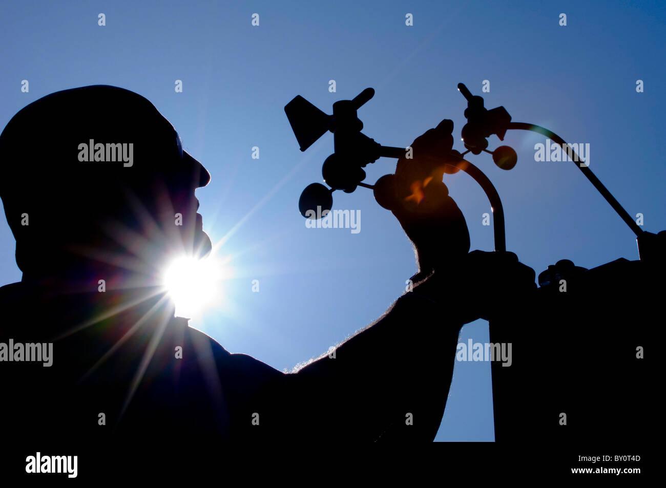 Uno specialista stagliano contro il cielo blu di installare una stazione meteo. Immagini Stock
