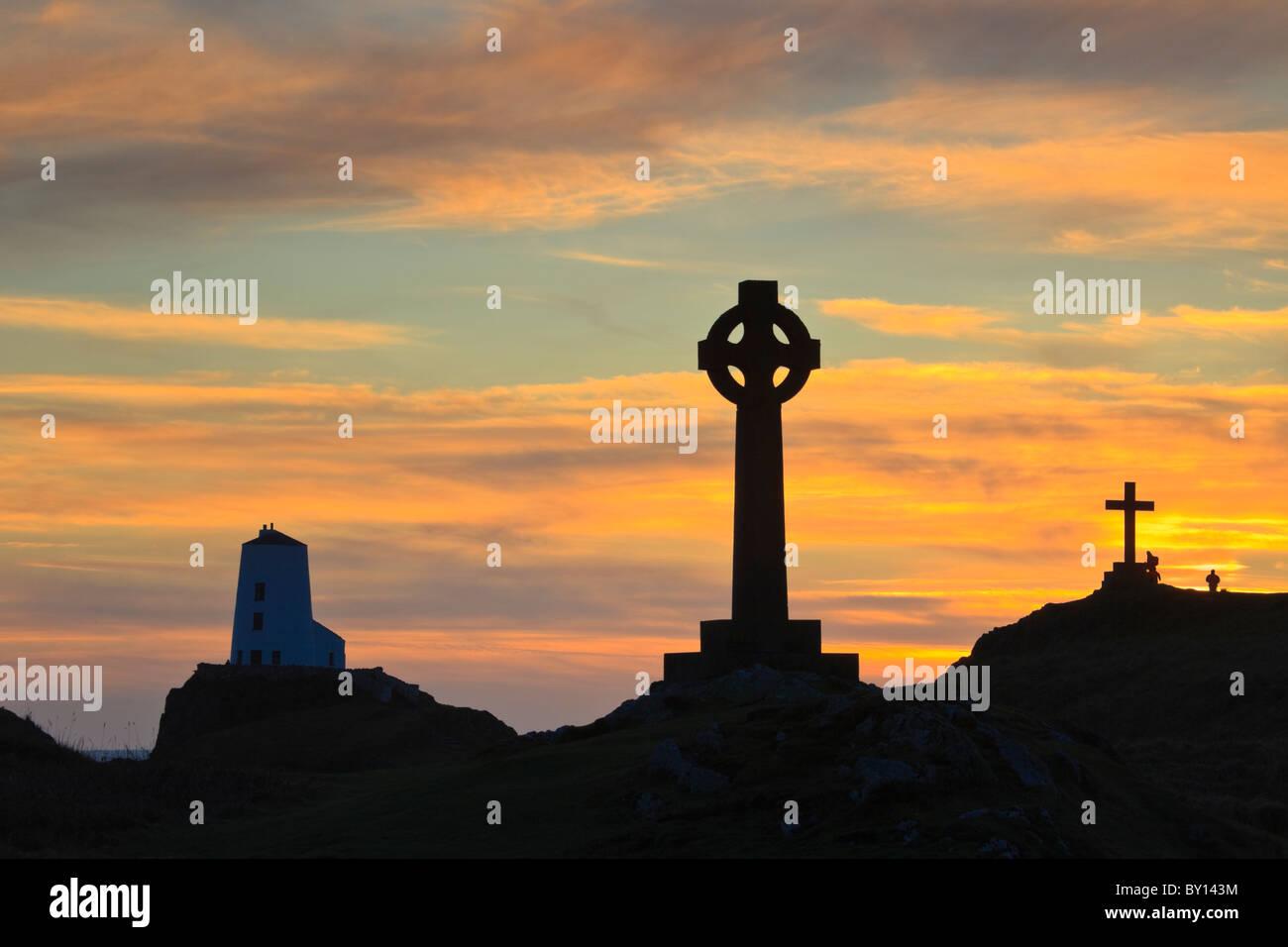 St Dwynwen croce celtica e Twr Mawr faro in silhouette sull isola di Llanddwyn al tramonto Isola di Anglesey, Galles del Nord, Regno Unito Foto Stock