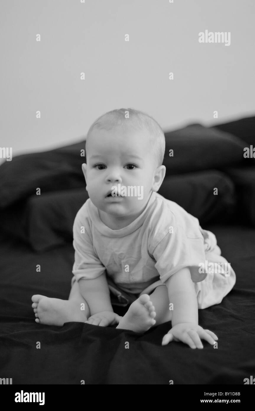 Bambino seduto in un letto grande Immagini Stock