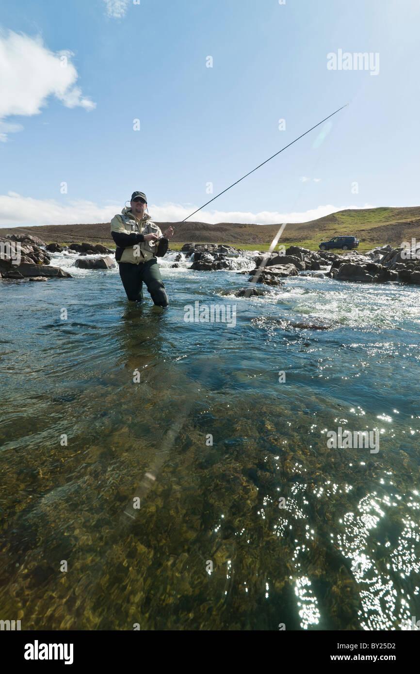 Pescatore a mosca la bobinatura in un salmone in un bellissimo ambiente in Islanda Immagini Stock
