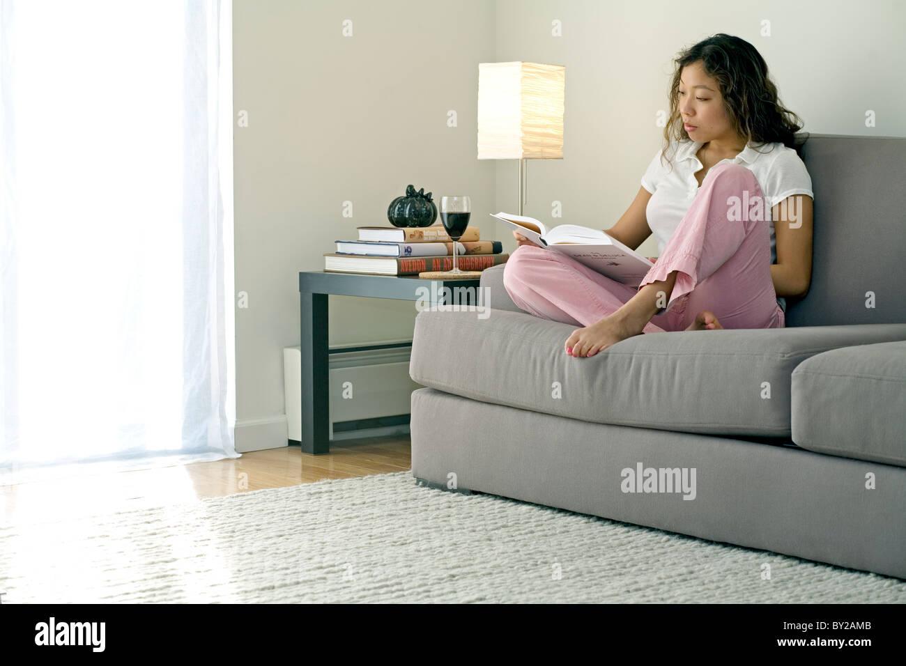 Una giovane donna la lettura sul divano di casa. Immagini Stock