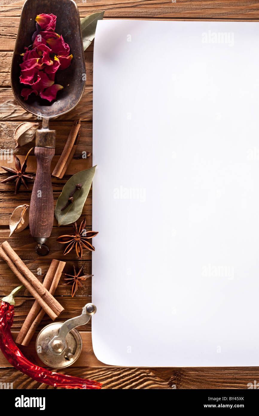 Immagine della carta bianca con spezie su una superficie in legno Immagini Stock