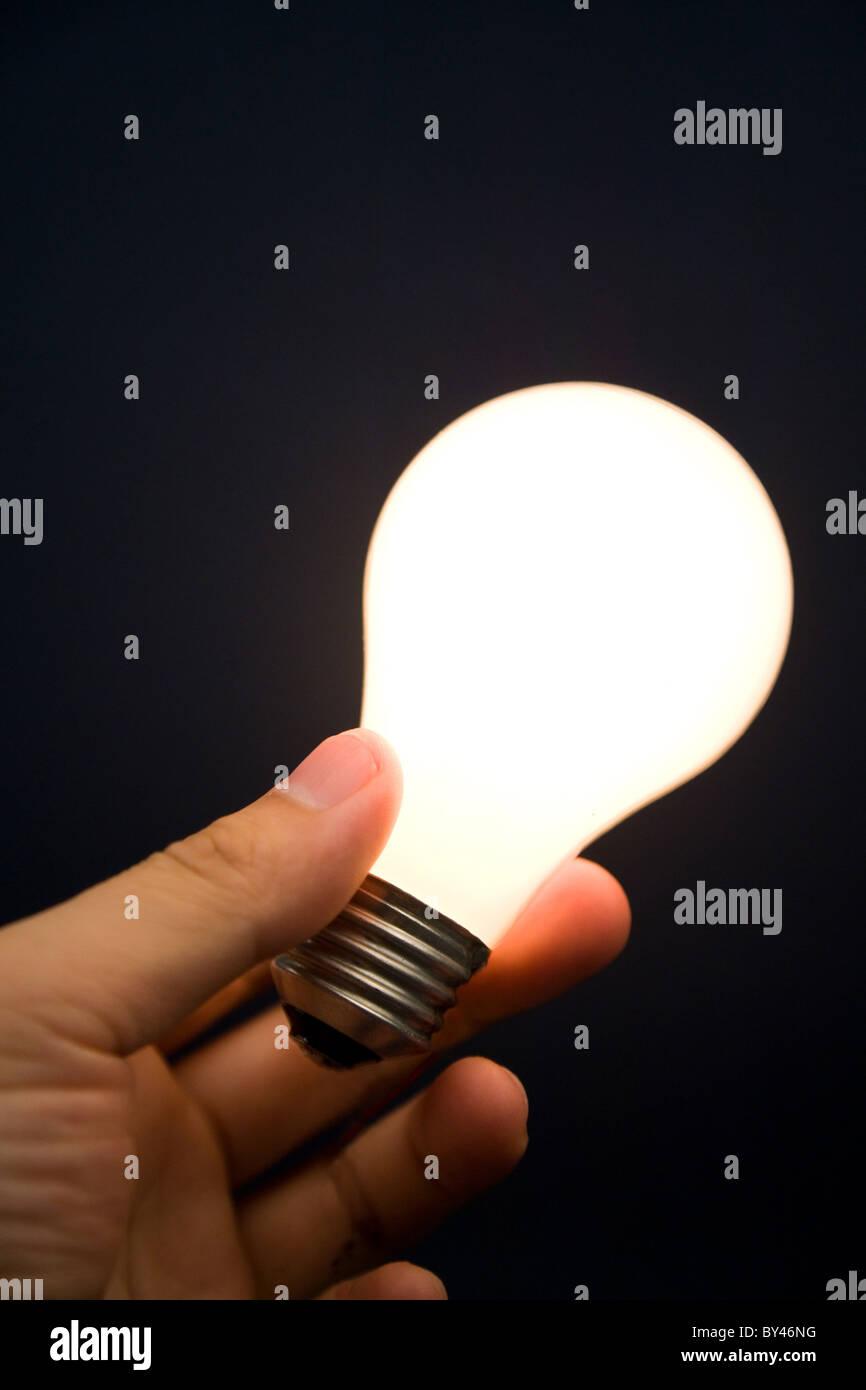 Mano che tiene una brillante luce della lampadina, concetto di ispirazione e idee Immagini Stock