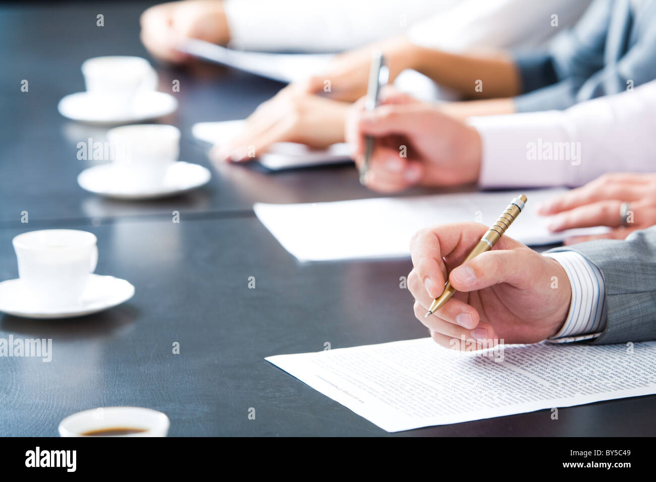 Stretta di mano maschile tenendo penna a sfera su documento aziendale su sfondo di mani umane con tazze di caffè Immagini Stock