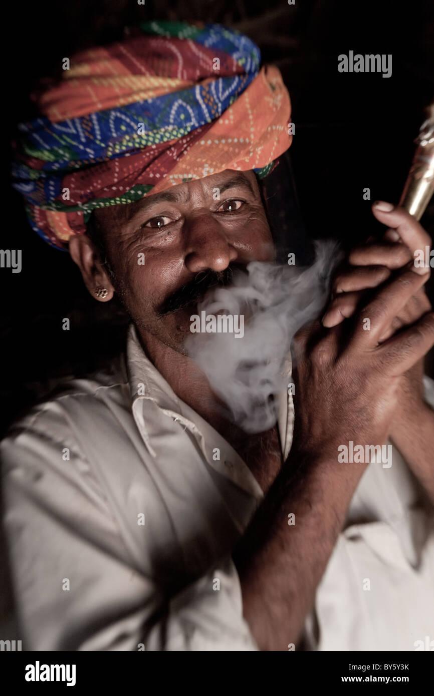 Uomo indiano (membro di Bishnoi setta religiosa) fumando una tubazione, nr Jodhpur, Rajasthan, India Immagini Stock