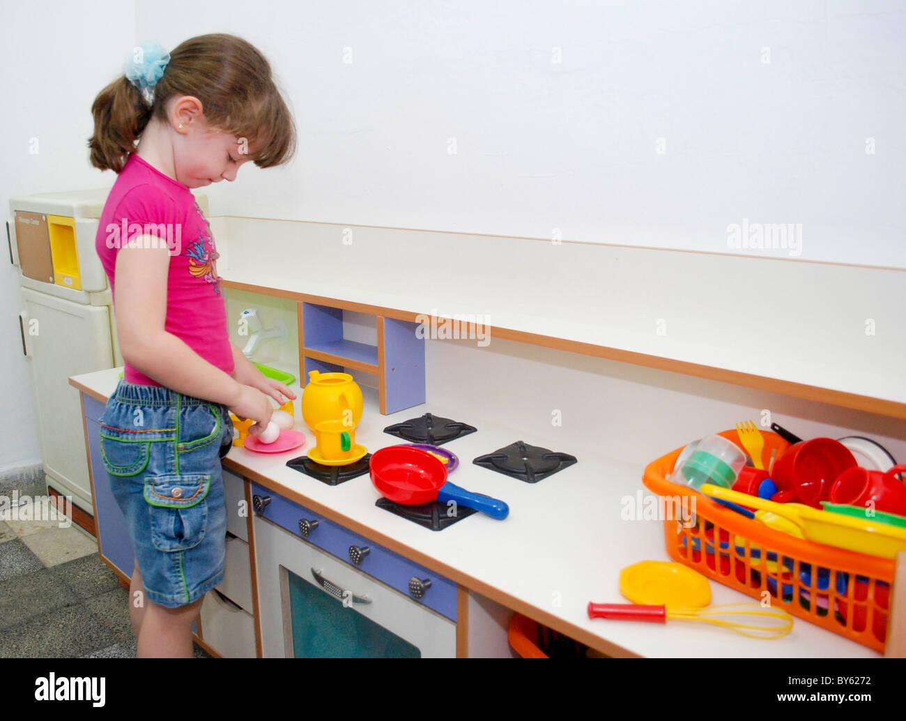 Ragazza in età prescolare di 5 gioca con un giocattolo cucina Immagini Stock