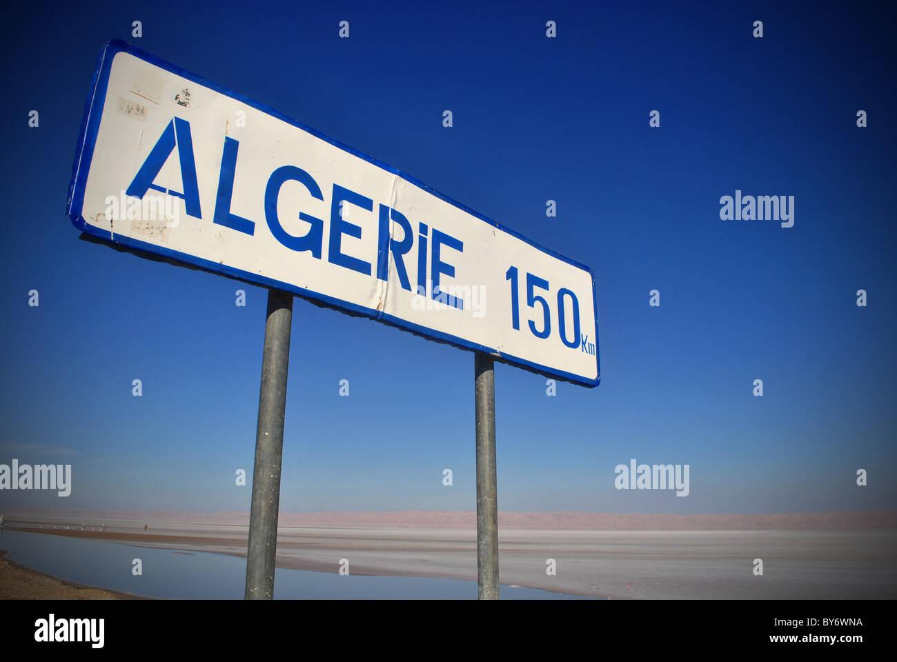 Un cartello stradale sul modo di Algeria vicino a Tozeur, Tunisia Immagini Stock
