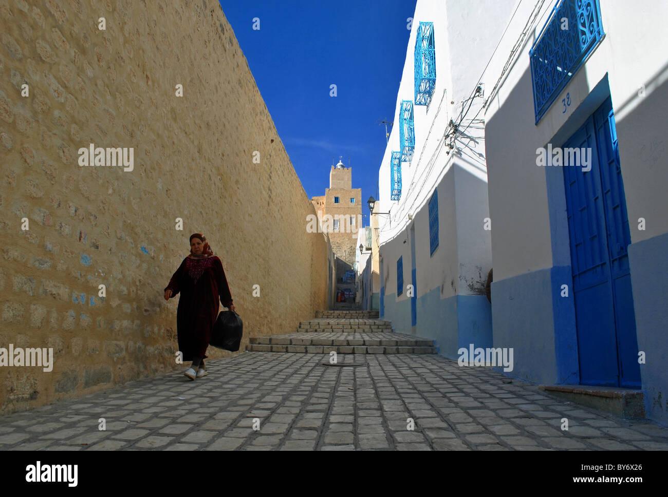 Donna che cammina giù per una strada in Sousse medina, Tunisia Immagini Stock