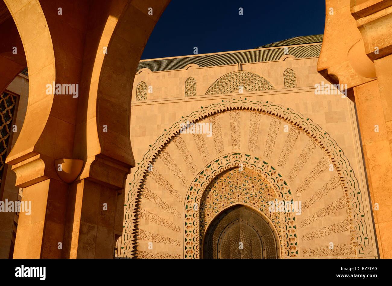Porta alla moschea di Hassan II casablanca al tramonto visto attraverso arcata in pietra del Marocco Immagini Stock
