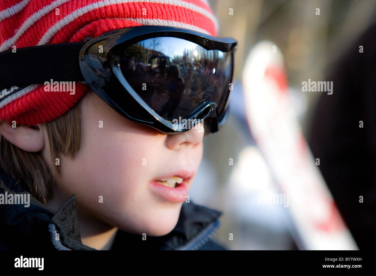 Bambino di otto anni che indossa googles e una Red Hat, prepararsi a sciare Immagini Stock
