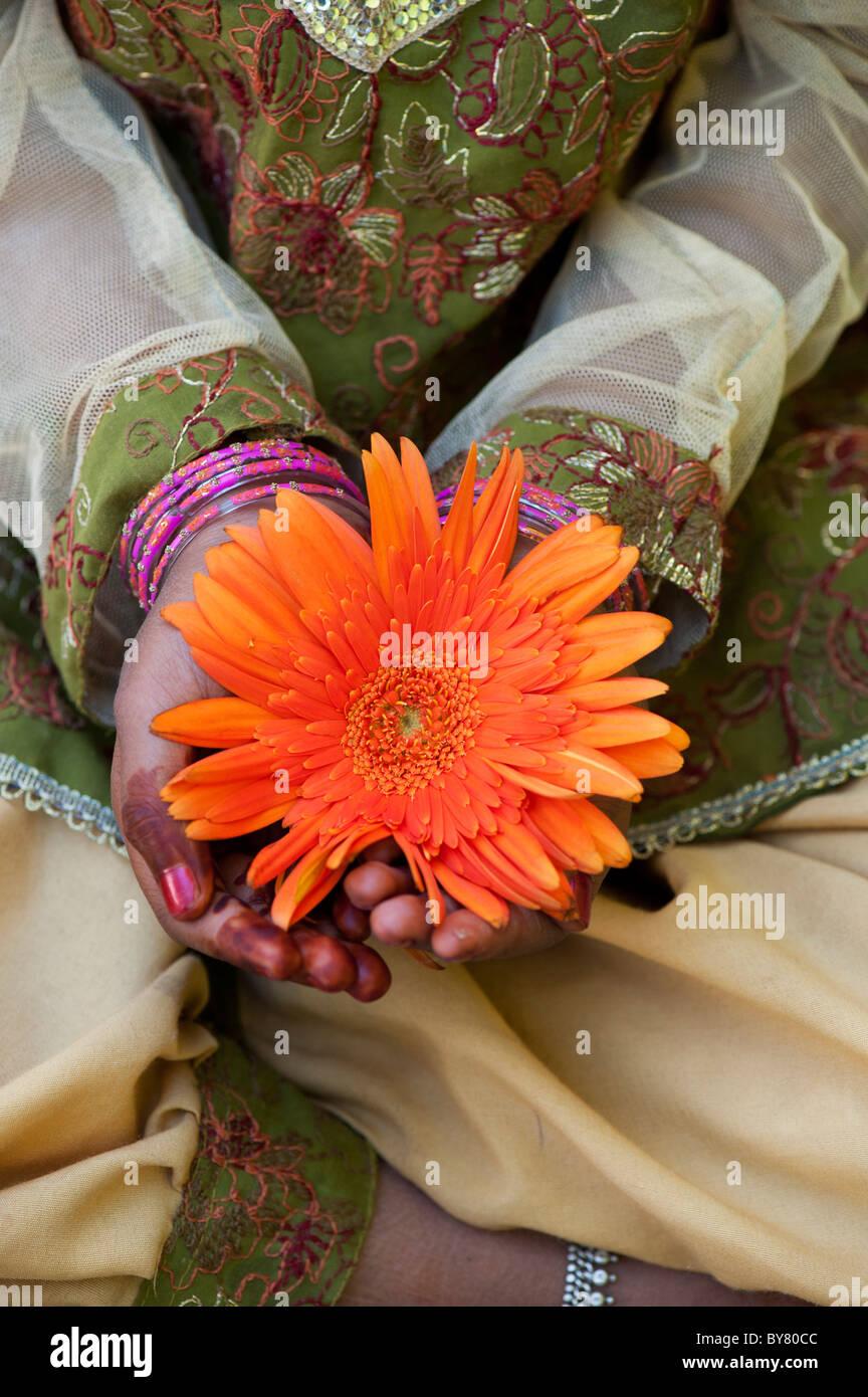 Giovane ragazza indiana tenendo un orange gerbera fiore. India Immagini Stock