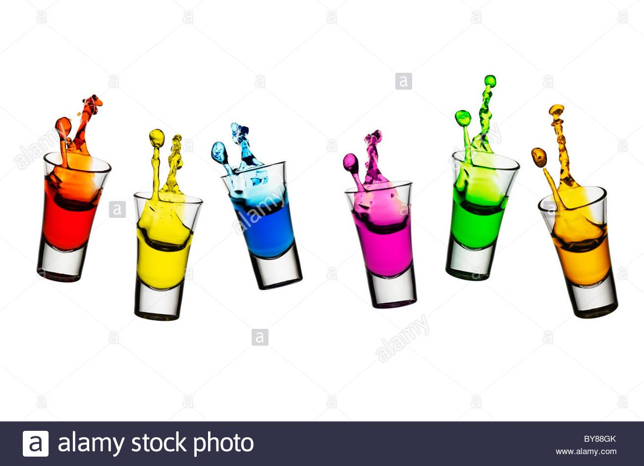 Liquore colorati fuoriuscita da bicchierini Immagini Stock