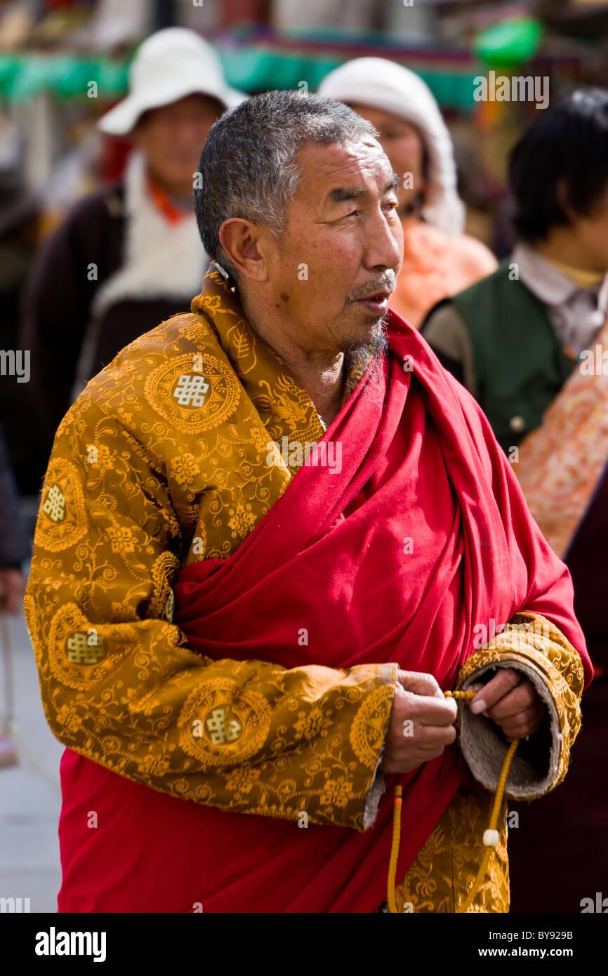 Vecchi uomini tibetano pellegrino indossando un rivestimento in oro rosso  con anta in Barkhor 1cd466db206f