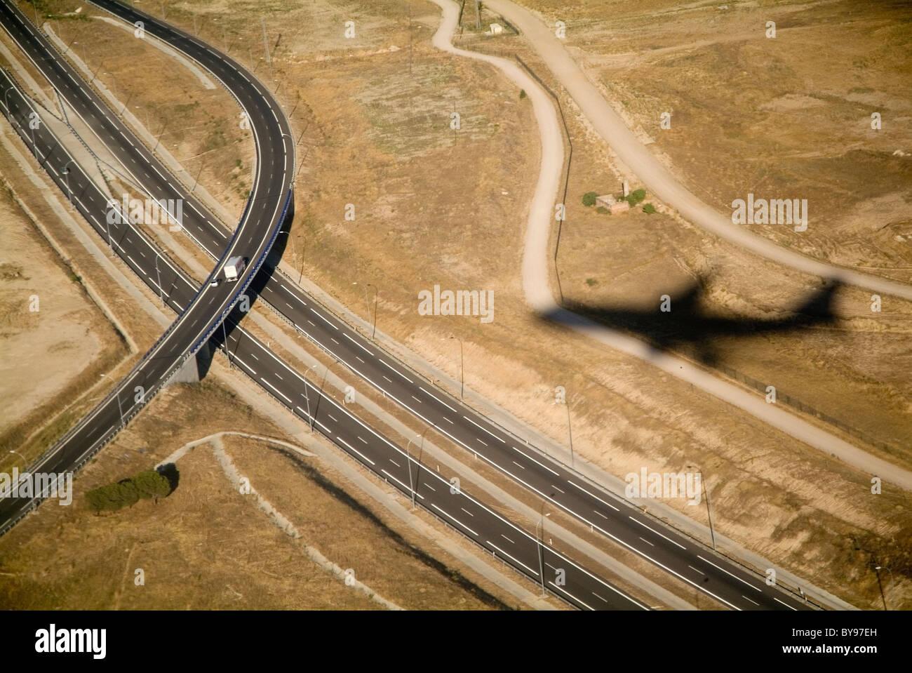 Forme di viaggio o di viaggio concetto - ombra di un aereo in volo su una grande autostrada, superstrada, autostrada Immagini Stock