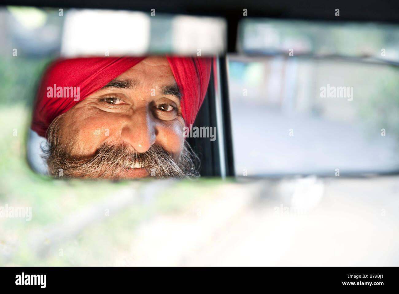 La religione sikh taxi driver esaminando lo specchietto retrovisore Immagini Stock