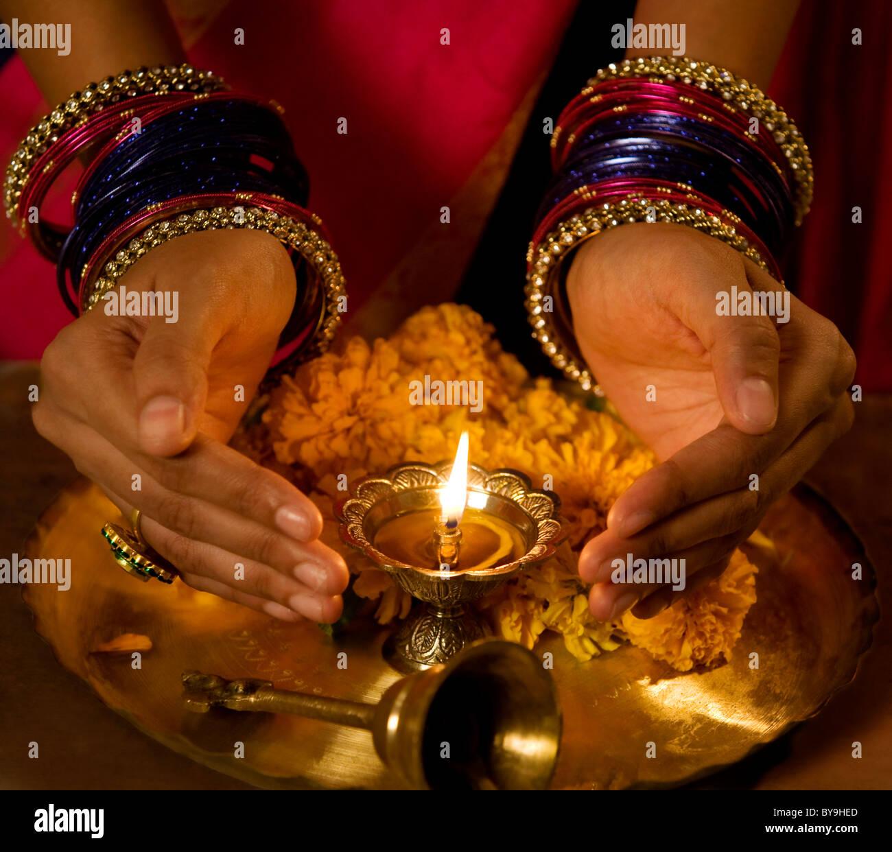 Le mani a coppa attorno a Diya Immagini Stock