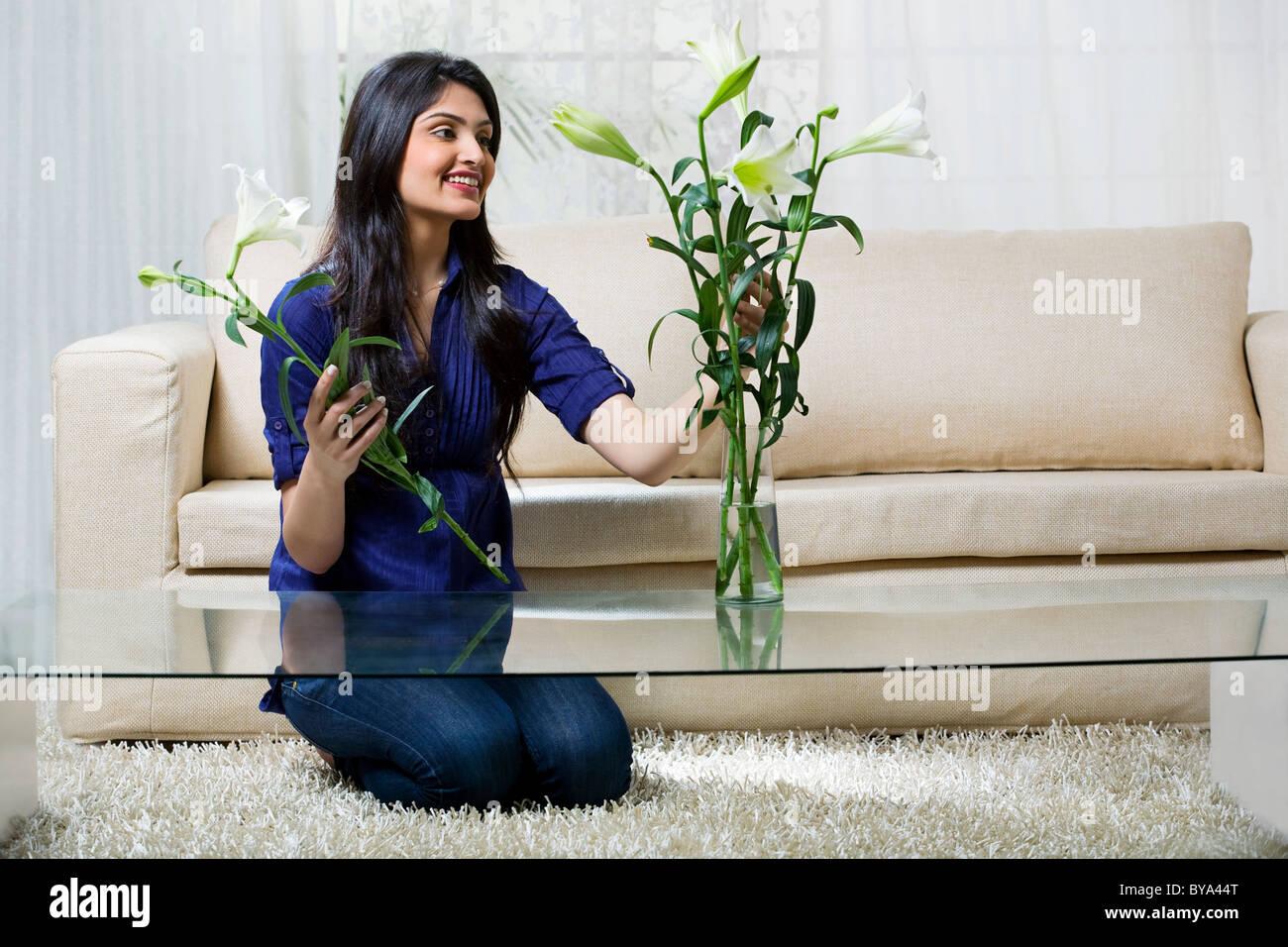 Giovane donna disponendo dei fiori in un vaso Immagini Stock